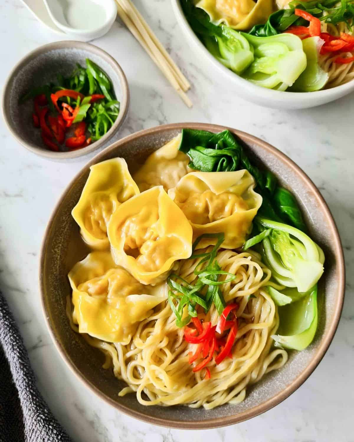 A bowl of wonton noodle soup topped with scallions and red chilli